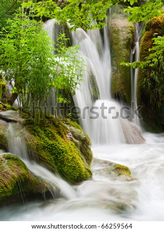 Waterfall currents in national park. Plitvice, Croatia. Popular touristic destination with lush vegetation. - stock photo