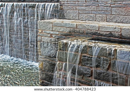 Waterfall from a fountain cascading over brickwork. - stock photo