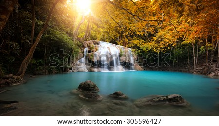 Waterfall in autumn forest with bright sun light and small natural lake with clear blue water  - stock photo