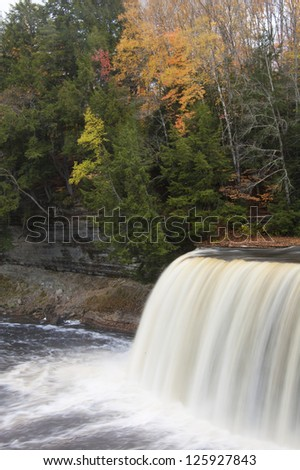 Waterfall in forest with autumn colors vertical, close up - stock photo