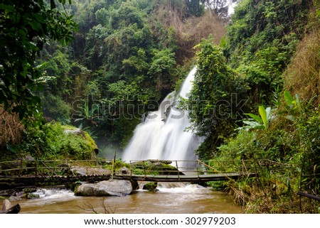 waterfall in forest with small bamboo bridge raining seasons - stock photo