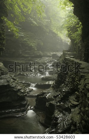 waterfall in gorge with misty rain and sunlight showing through the trees - stock photo