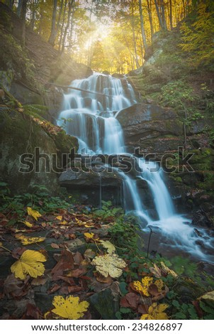 Waterfall in the Carpathian autumn forest. Blue clean water with motion blur - stock photo