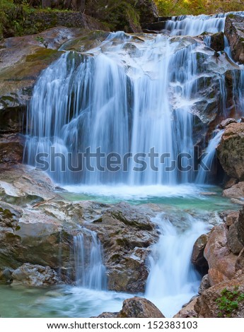 Waterfall in the mountain forest - stock photo