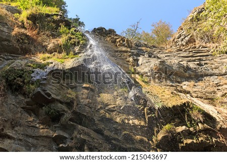 Waterfall in the mountains - stock photo