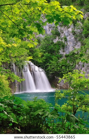 Waterfall into a green lake. Branches of a tree and green leaves as foreground. - stock photo