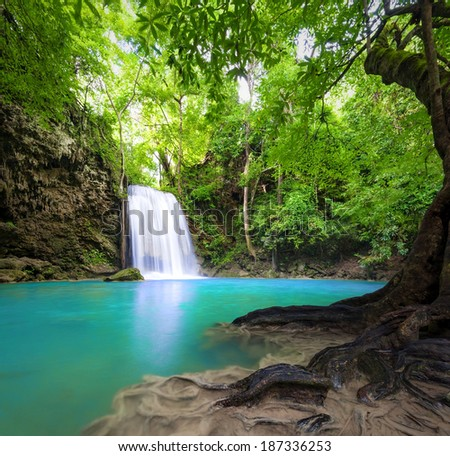 Waterfall landscape background. Beautiful nature outdoor photography. Thailand green rain forest jungle with trees and bushes, fresh clean and cool water river flows through stones cascades and roots - stock photo