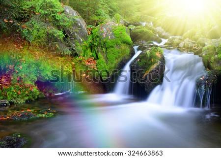 Waterfall on a mountain creek with rainbow. National park Sumava-Czech Republic - stock photo