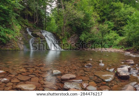 waterfall on mountain in summer time - stock photo