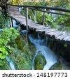 waterfall under an old wooden bridge - stock photo