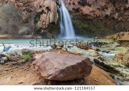 Waterfall with boulder in the foreground - stock photo