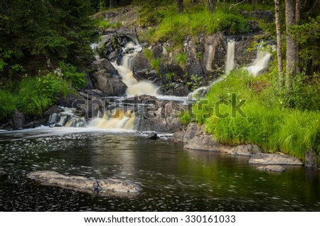 waterfall with cascades in the forest - stock photo