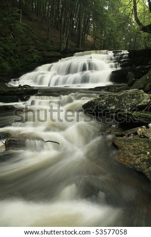 waterfall with stream over rocks through woods - stock photo