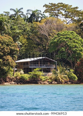 Waterfront Caribbean home surrounded by lush tropical vegetation, Bocas del Toro, Panama - stock photo