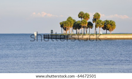 Waterfront entrance to the St. Pete Bay, with some palm trees alongside a beach walkway, on a sunny day. - stock photo
