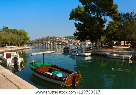 Waterfront panoramic view of Trogir in Croatia, in a bright sunny day with fishing boats ifloating on the still crystal clear waters. - stock photo