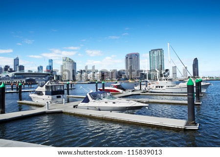 Waterfront's harbor with some yacth on dock and Etihad Stadium at background - stock photo