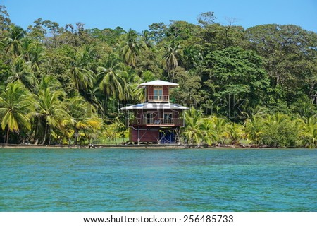 Waterfront tropical house and vegetation on the Caribbean island of Bastimentos, Bocas del Toro, Panama, Central America - stock photo