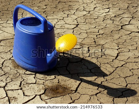 watering can full of water on dry cracked soil - stock photo