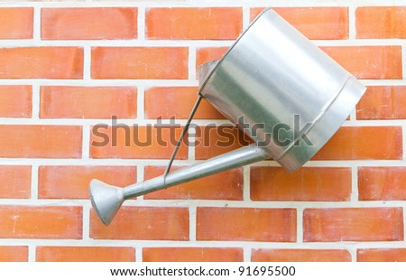 watering can hanging on the vintage wall - stock photo
