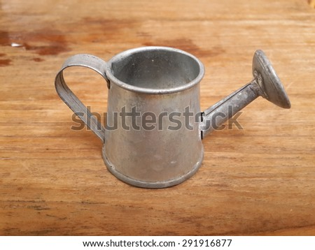 watering can on  wooden table - stock photo