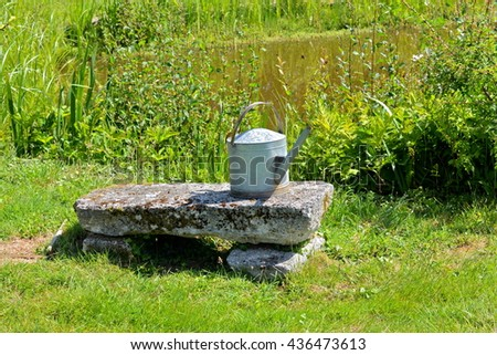Watering can, vintage, on a freestone bench - stock photo