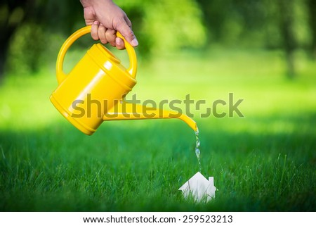 Watering can watering cardboard house - stock photo