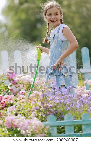 Watering, summer joy - beautiful girl watering roses with garden hose  - stock photo