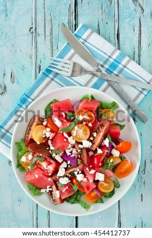 Watermelon and tomato salad with feta cheese, overhead scene on rustic blue wood - stock photo