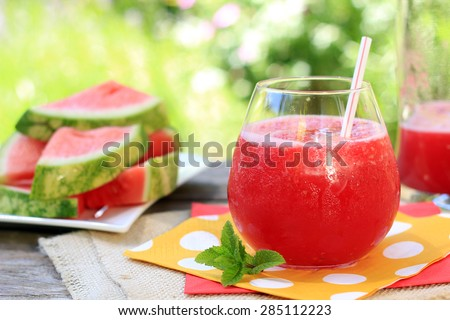 Watermelon drinks outside in the garden with straws and fresh mint. Also available in vertical.  - stock photo