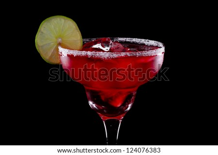 watermelon margarita served over ice in a dark bar garnished with salt and a lime - stock photo