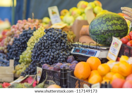 Watermelon on weighing scale machine and grapes, oranges, apples and plums on city market - stock photo