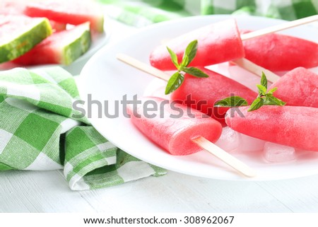 Watermelon popsicle on plate on white wooden table - stock photo