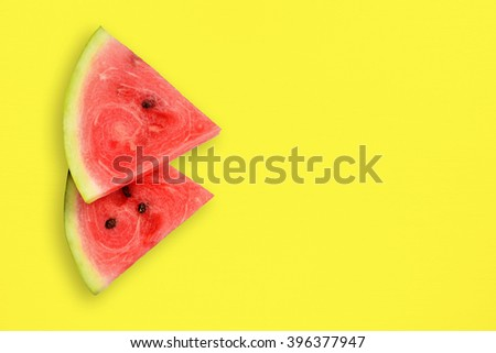 Watermelon slices on yellow table - stock photo