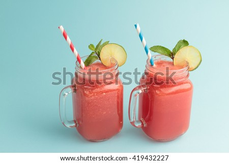 Watermelon smoothie in Mason jars with lime and mint on blue background - stock photo