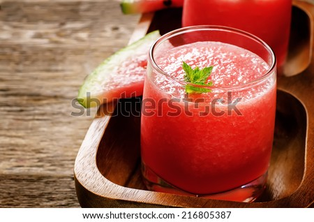 watermelon smoothie on a dark wood background. tinting. selective focus on mint - stock photo