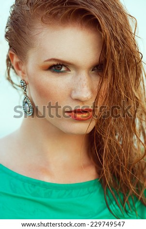 Waterproof cosmetics concept. Fashion portrait of young model with wet long red hair in azure summer dress. Perfect skin with freckles and stylish make-up. Luxurious earrings. Close up. Outdoor shot - stock photo