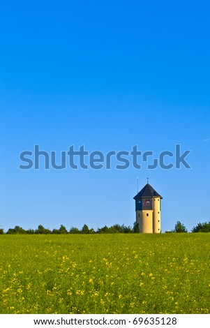 watertower with rapeseed field in blue sky - stock photo