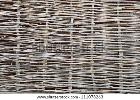 Wattle fence of dry twigs in the background - stock photo
