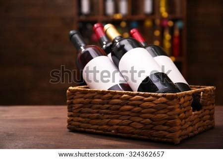 Wattled basket with labeled bottles of wine on unfocused dark background - stock photo