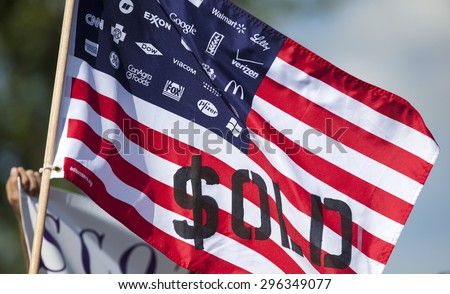 WAUKESHA, WI/USA - July 13, 2015: A flag protesting corporate spending in American political elections in front of the Waukesha Convention Center during a progressive political protest. - stock photo