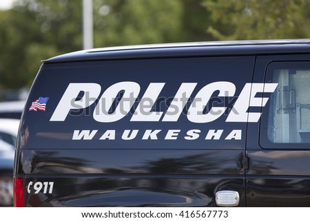 WAUKESHA, WI/USA - July 13, 2015: A Waukesha police van is parked in front of the Waukesha Convention Center during a progressive political protest against Governor Scott Walker. - stock photo