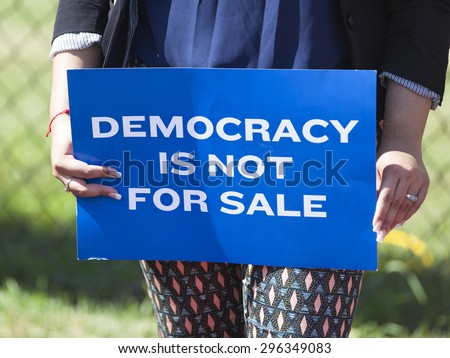 WAUKESHA, WI/USA - July 13, 2015: A woman holds a protest sign in front of the convention Center where Governor Scott Walker is about to make his 2016 Presidential announcement. - stock photo