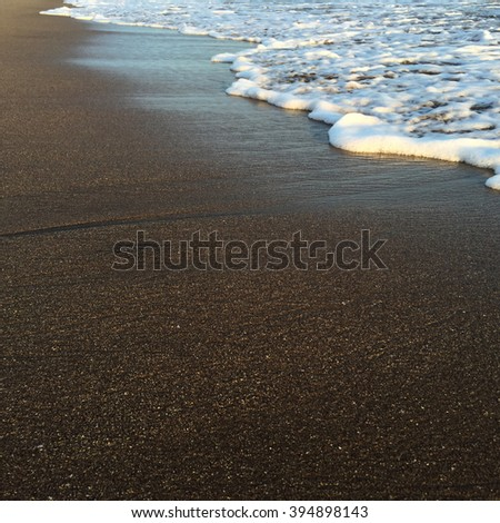Wave and beach, shiny tropic sea wave on the beach sand in sunset light, summer holiday, beach life, white foam wave and yellow sand, close up of beach and sea wave, beach holiday, quiet sea, Bali - stock photo