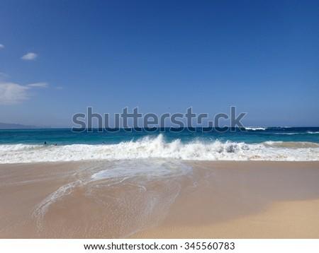wave beach on shore of Baldwin Beach looking towards Oean with plane flying overhead on Maui, Hawaii - stock photo