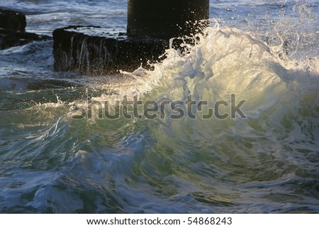 Wave breaking with sun catching water droplets - stock photo