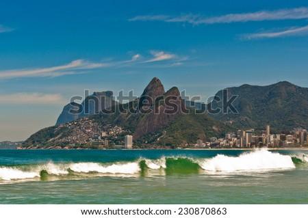 Wave in the Ocean at Ipanema Beach with Beautiful Rio de Janeiro Mountains on Horizon - stock photo