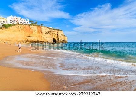 Wave on sandy beach in Carvoeiro fishing village, Algarve, Portugal - stock photo
