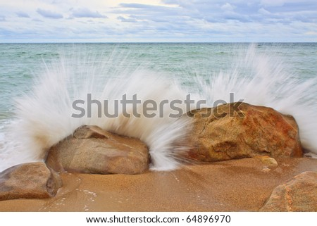 wave sends spray into the air after crashing into rocks with stormy sky - stock photo