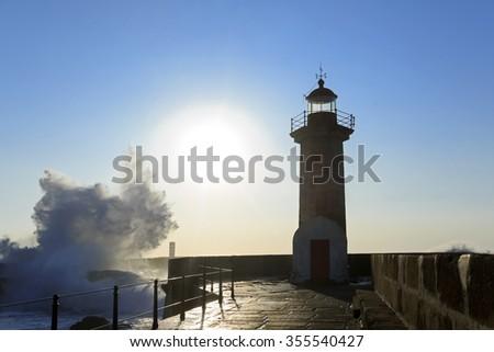 Wave splash at sunset near lighthouse, Porto, Portugal - stock photo